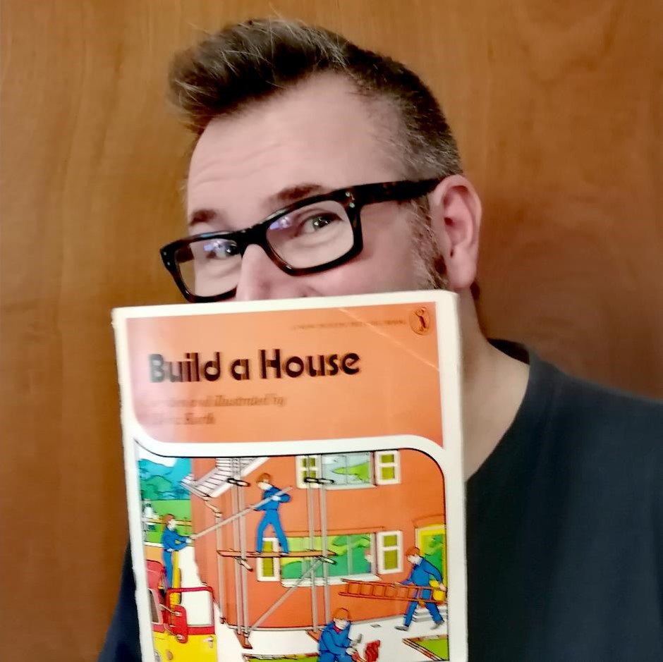 Tim Hoskins of Turner & Hoskins Architects holding a copy of Build A Home